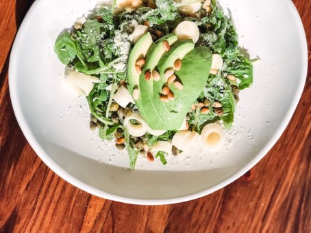 hearts of palm salad garnished with avocado and pine nuts