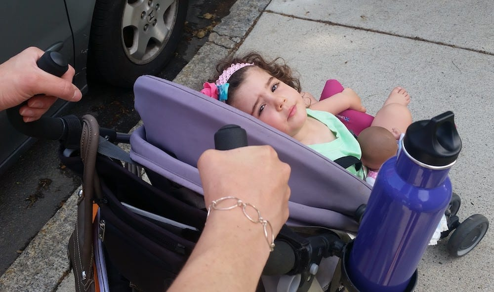 Pushing toddler in a stroller with reusable water bottle