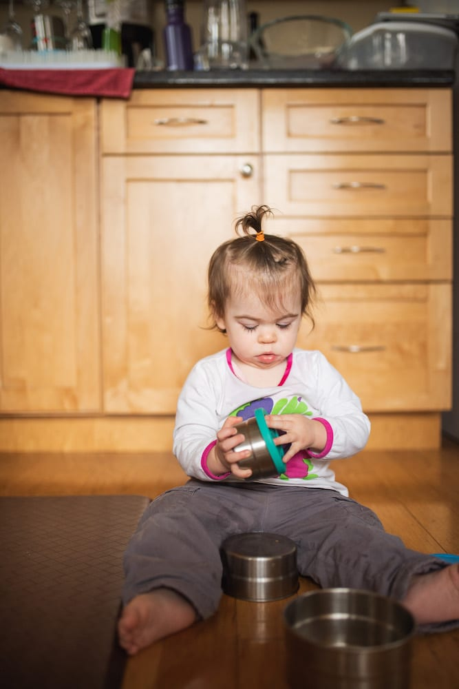 toddler in a kitchen playing with a set of steel food containers