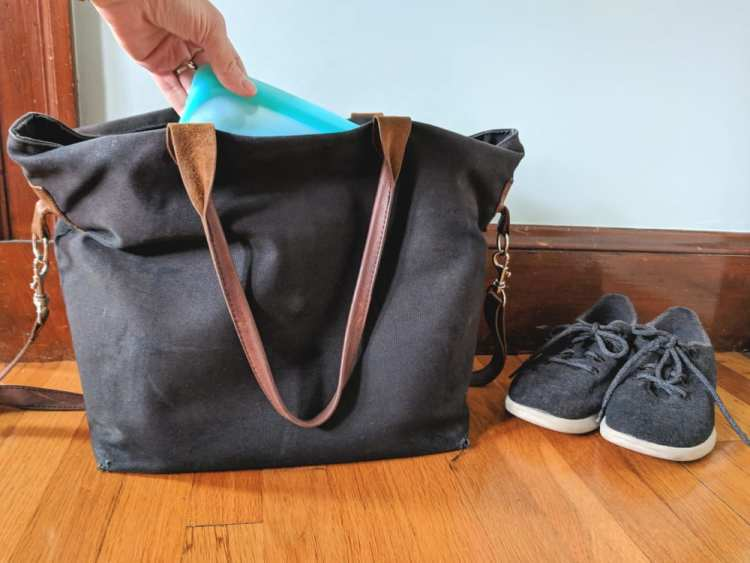 Hand putting reusable container in black canvas bag with pair of gray sneakers next to it