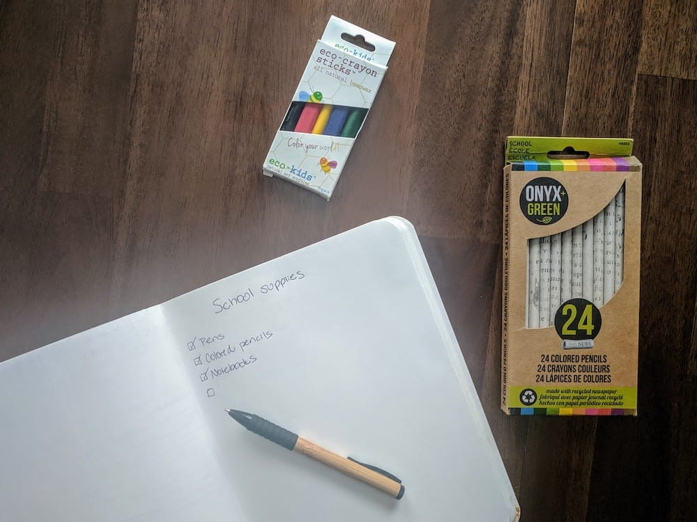 eco-crayon sticks, colored pencils, and notebook with school supplies on a wood desk