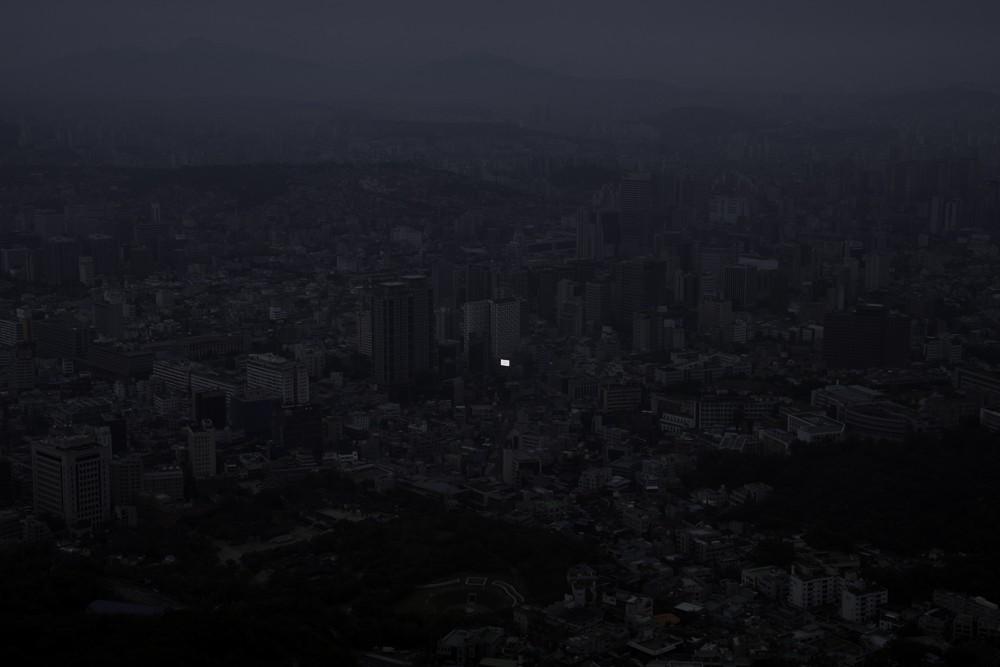 photographie d'un panneau de pub allumé dans la nuit