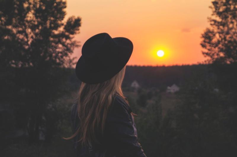 Woman staring at a beautiful sun