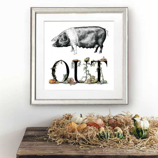 Print of a saddleback pig and lettering decorated with vegetables in a white frame on a white wall above a wooden shelf