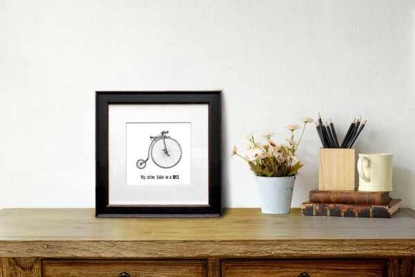 Print of a black and white drawing of a penny farthing in a black frame on a wooden desk leaning against a white wall