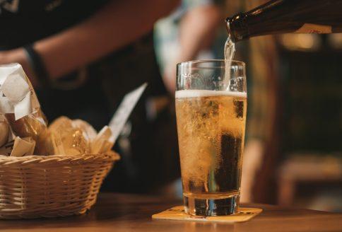 Bier wird aus einer Flasche in ein Glas gefüllt