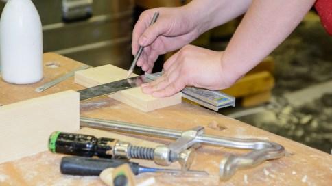 Holzstück wird gemessen und markiert