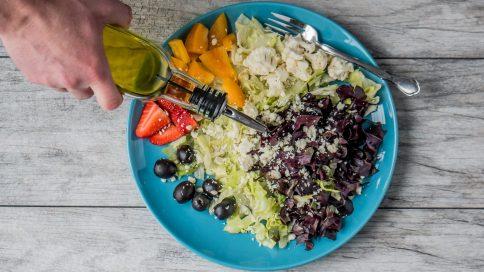 Gemischter Salat auf einem Teller, Öl wird darüber geträufelt