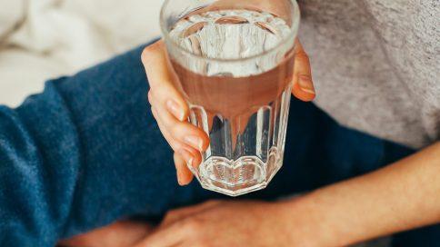 Person hält ein Wasserglas
