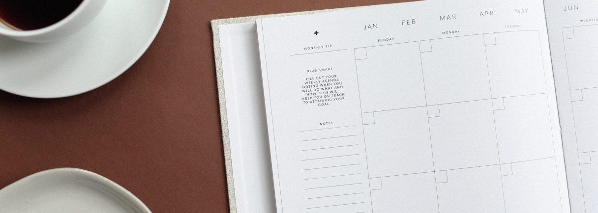 Kaffeetasse, Büroklammern und Kalender auf einem Tisch