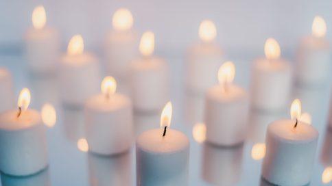 Viele kleine brennende weiße Kerzen nebeneinander