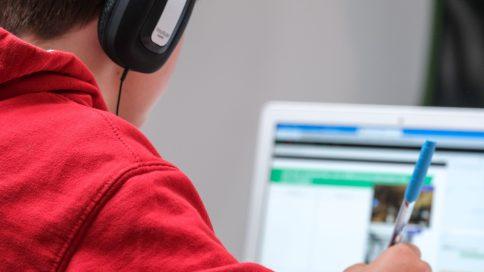 Junge mit Kopfhörern vor Laptop