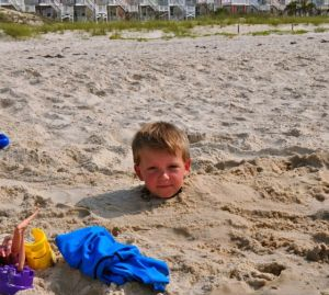 Boy buried in sand up to his neck