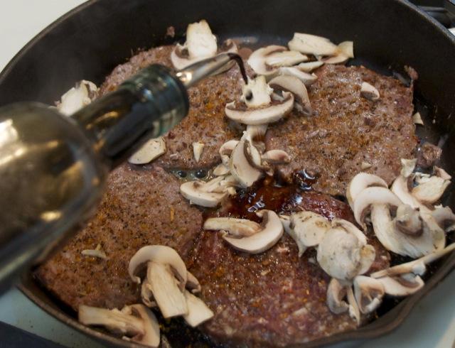Patties and mushrooms frying