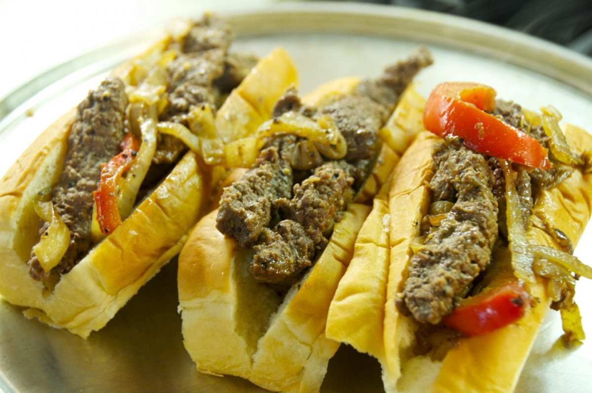 cubed steak, onions and peppers in hot dog buns