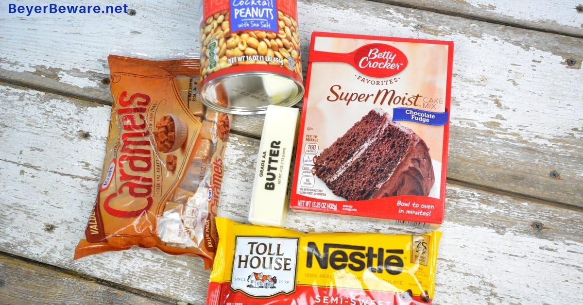 Snickers cake recipe takes a chocolate cake mix up a notch by filling it with caramel, peanuts and chocolate chips making for the cake version of a favorite candy bar. #CakeMix #Snickers #Caramel #Chocolate