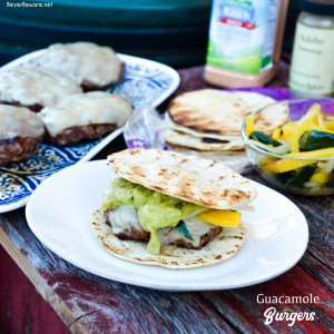 Guacamole burgers combine taco night with burger night straight from the grill with flavorful burgers, pepper-jack cheese, guacamole, sauteed onions, peppers, and street taco tortilla shells.