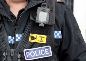 Close-up of police uniform jacket with body camera and yellow patch with camera icon and text stating Video and Audio.