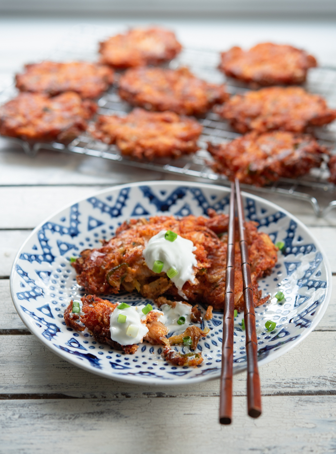 Cheesy Kimchi Potato Pancakes are served with sou cream on a plate.