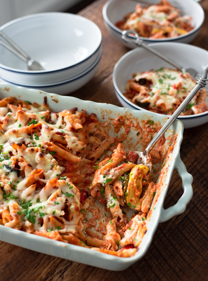 Baked Pasta with Ricotta and Roasted Vegetables are spooned up to serve in a bowl.