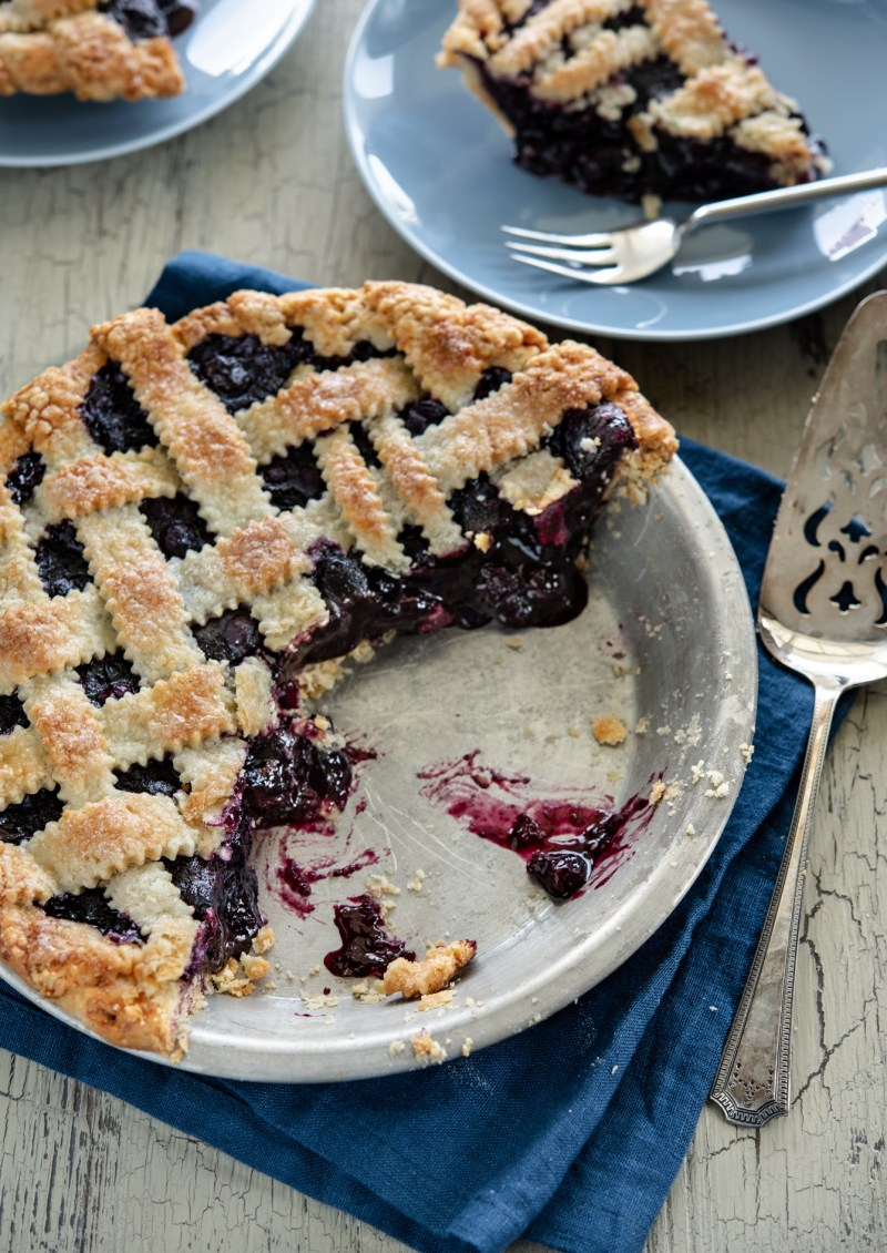 Maple blueberry pie with lattice top crust is cut and served.