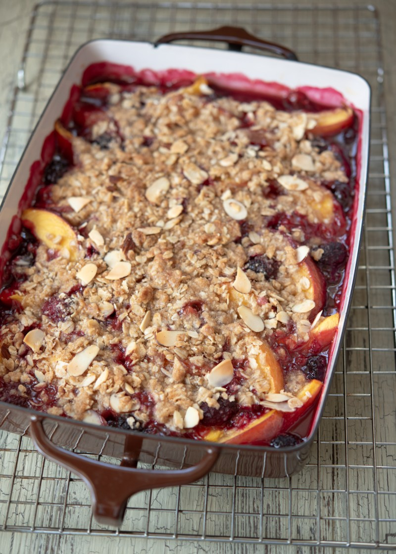 Warm nectarine blackberry crisp is cooling on a wire rack.