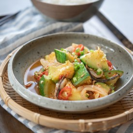 Korean round zucchini and anchovy side dish is served in a small bowl on a woven patter