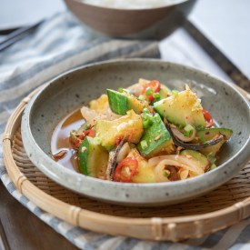 Zucchini squash and dried anchovy side dish is served on a grey plate in a woven platter