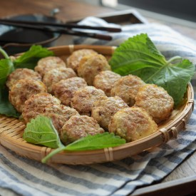 Korean mini patties made with ground pork and tofu are resting on a bamboo plate
