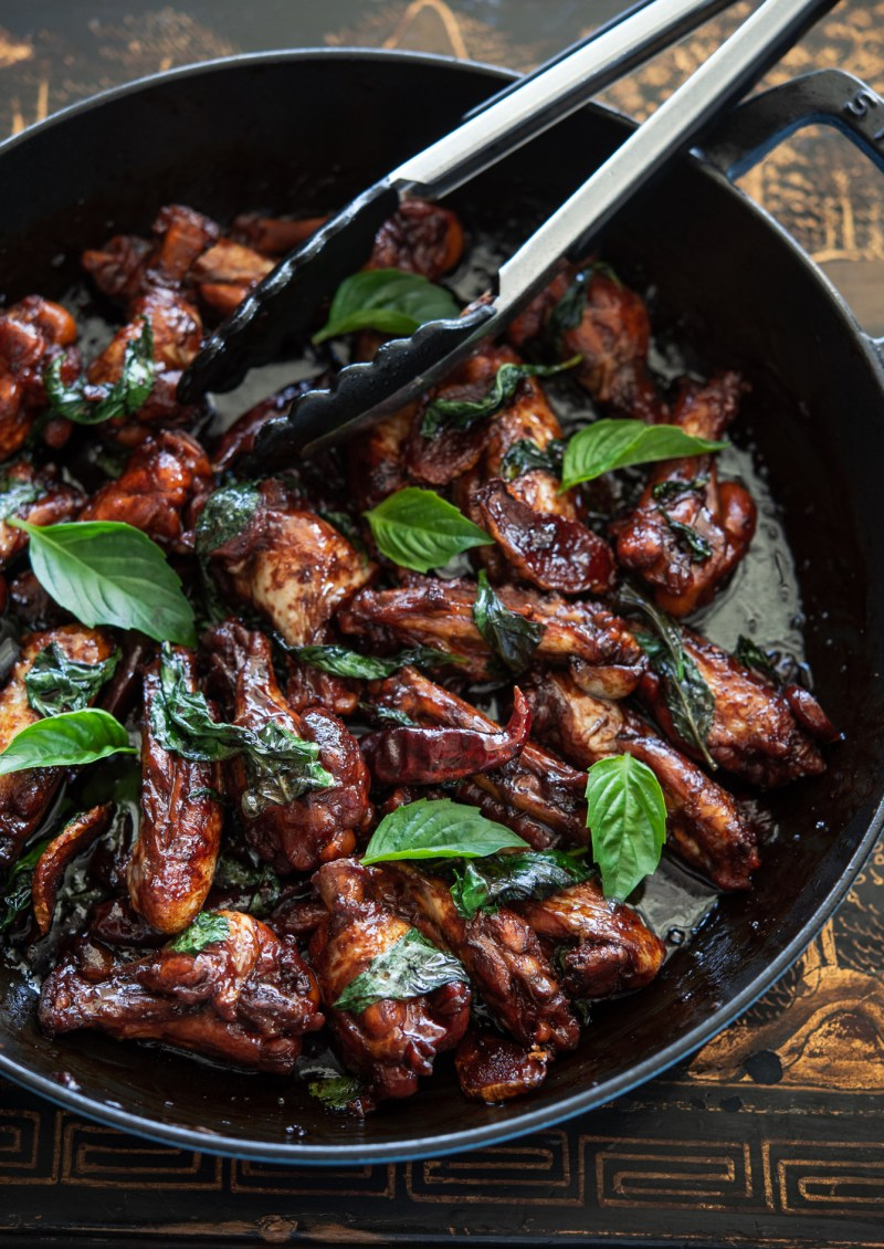 Taiwanese style chicken party wings (san bei ji) are garnished with Thai basil leaves.