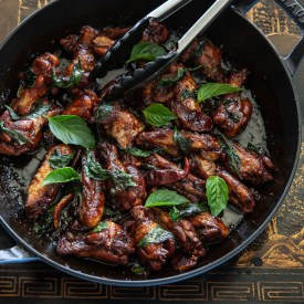Taiwanese three cup chicken (san bei ji) is garnished with Thai basil leaves.