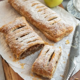 A slice of puff pastry apple strudel has flaky crust with soft apple filling inside.