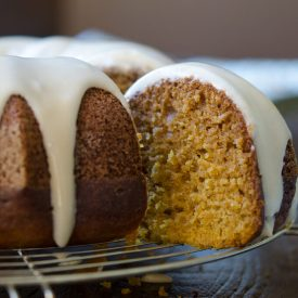 A slice of pumpkin bundt cake with maple glaze shows moist and tender crumbs