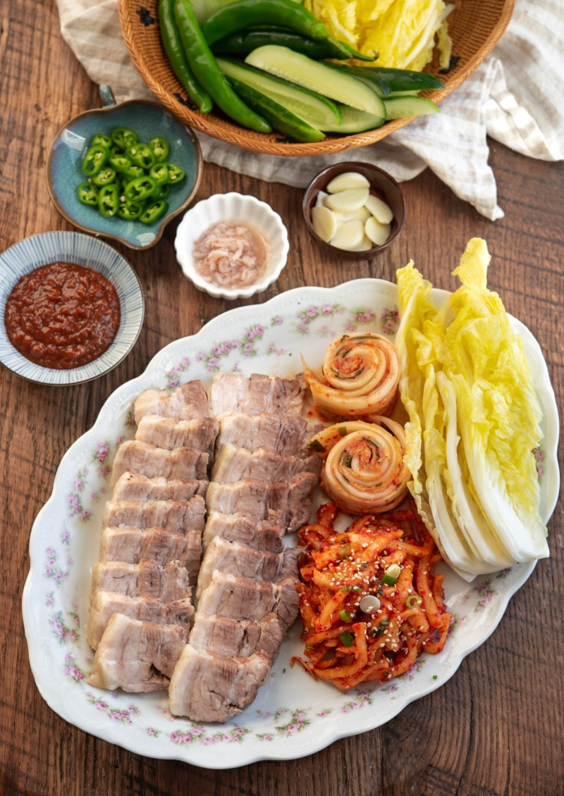 Korean bossam is arranged in a platter with cabbag leaves, radish salad, and toppings to make wraps