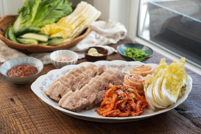 Korean bossam abd radish salad is arranged with pickled cabbage to make bossam wraps
