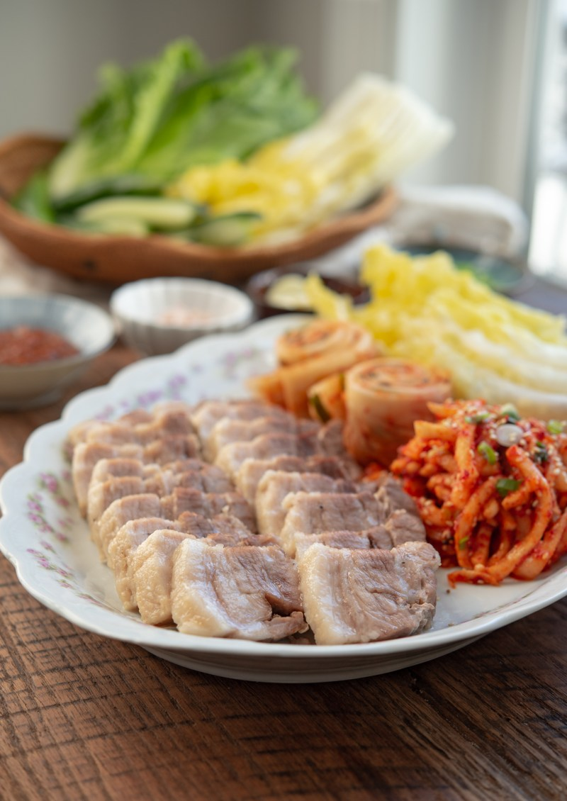 Slices of pork belly and radish salad, and cabbage leaves are arranged to make Korean bossam