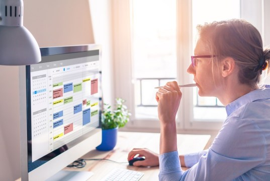 A woman staring at a calendar on her computer