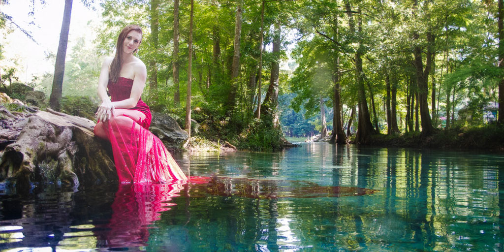 Hawaii Conceptual Portrait woman in red gown near water sitting on tree