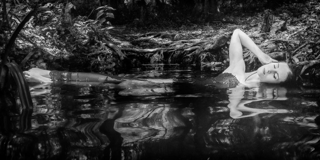 Hawaii Conceptual Portraitblack and white woman in gown laying in water with reflection