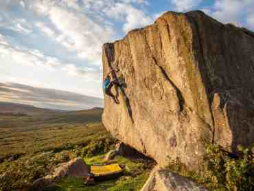 A man bouldering on Stanage Edge in the Peak District
