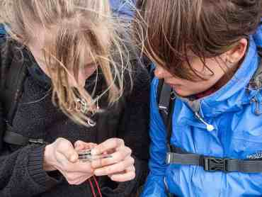 Two girls learning to use a compass and map read on an Introduction to Navigation course