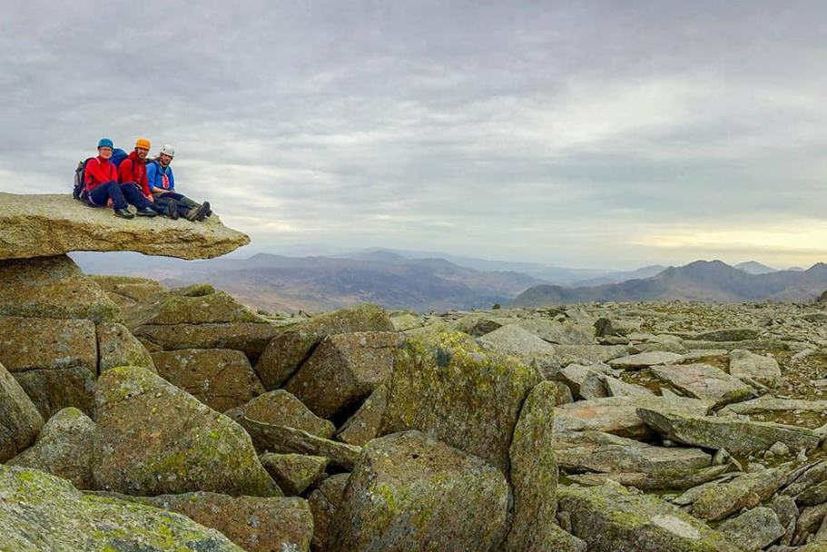 Three people sit on the cantilever stone on the summit of Glyder fach after scrambling up Chasm face, a classic Grade 3 scramble in Snowdonia