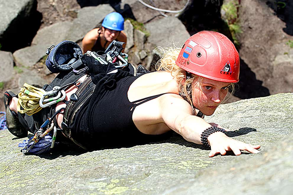A lady on a learn to lead climb course on Stanage Edge in the Peak District