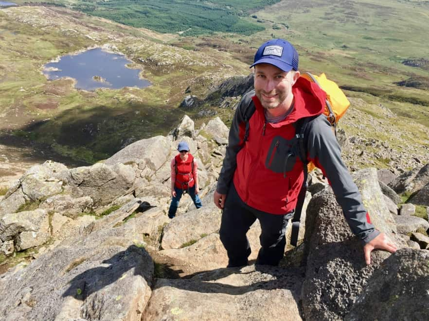 A man scrambles up Moel Siabod on a Mountain Skills course in Snowdonia.