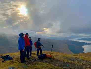 Four people on a mountain top looking down a Loch on a guided walking holiday in Scotland.