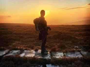 A lady walking in the sunset on the Edale Skyline Challenge