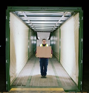 LTL Freight-Person holding a box inside of an empty freight truck.