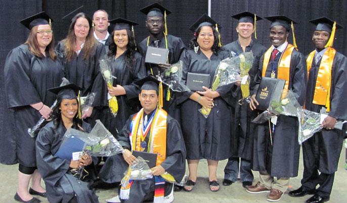 TRiO students at graduation holding diplomas