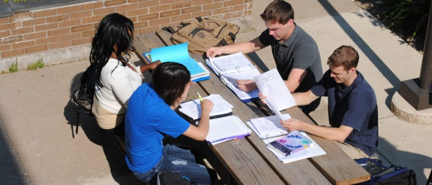 Students studying outside at a picnic table