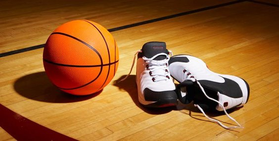 orange basketball ball next to basketball shoes